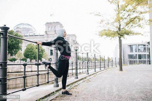 istock Muslim woman stretching her legs before running 999805674