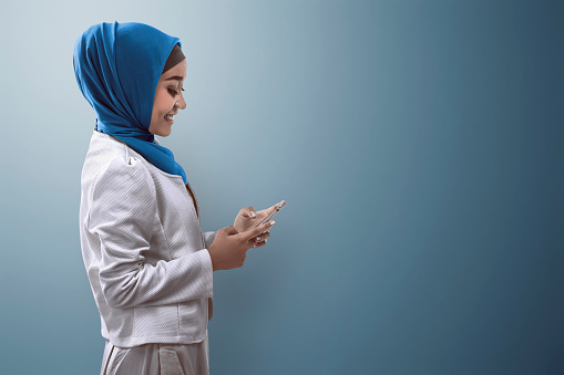 istock Muslim woman typing on cellphone 540221286