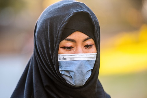 Serious Muslim woman wearing a protective face mask and a hijab