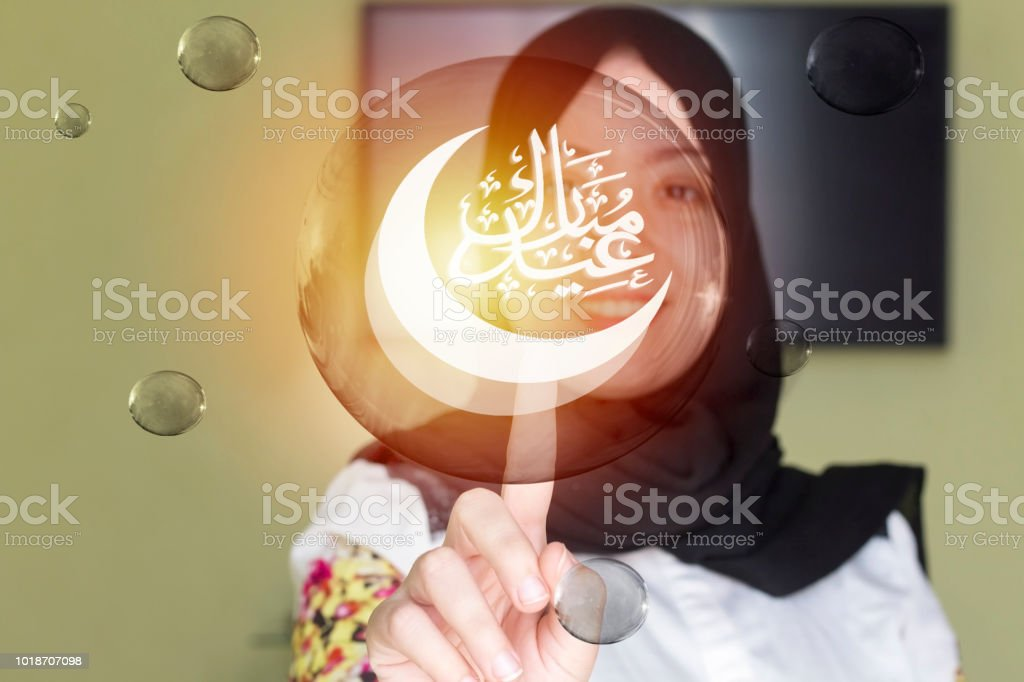 muslim woman wearing black scarf and pointing her finger to eid mubarak calligraphy  in transparent bubble stock photo