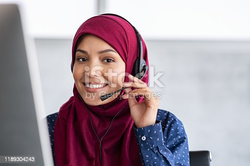 Portrait of happy young islamic woman in headscarf holding microphone and working on computer. Arab businesswoman working in customer service center talking using headset. Portrait of beautiful arabic woman in hijab smiling and looking at camera while working in office with copy space.