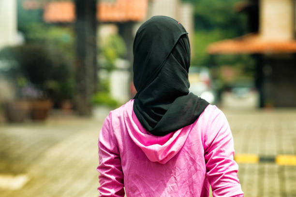 Muslim woman wearing Hijab in residential area rear shot Rear shot Muslim woman wearing Hijab in residential area religious veil stock pictures, royalty-free photos & images