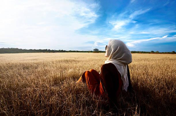 Muslim woman wearing hijab relaxing on savanna stock photo