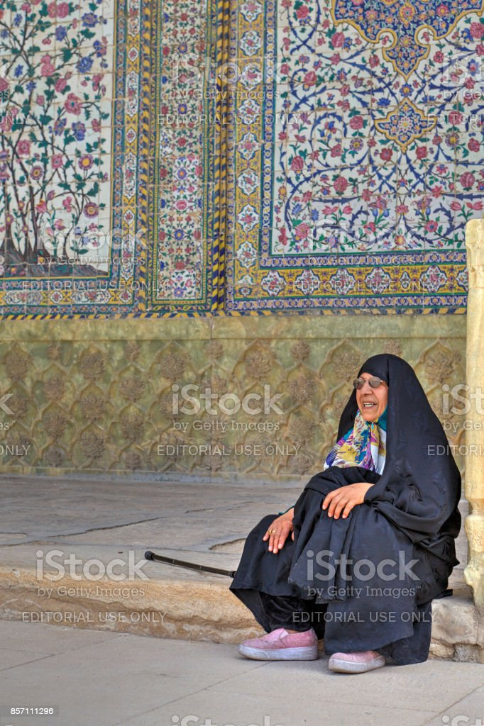 Muslim woman, wearing in Islamic clothing, sits inner courtyard Mosque. stock photo