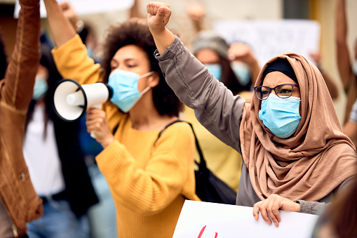 Muslim woman wearing protective face mask and supporting anti-racism movement with group of people on city streets.