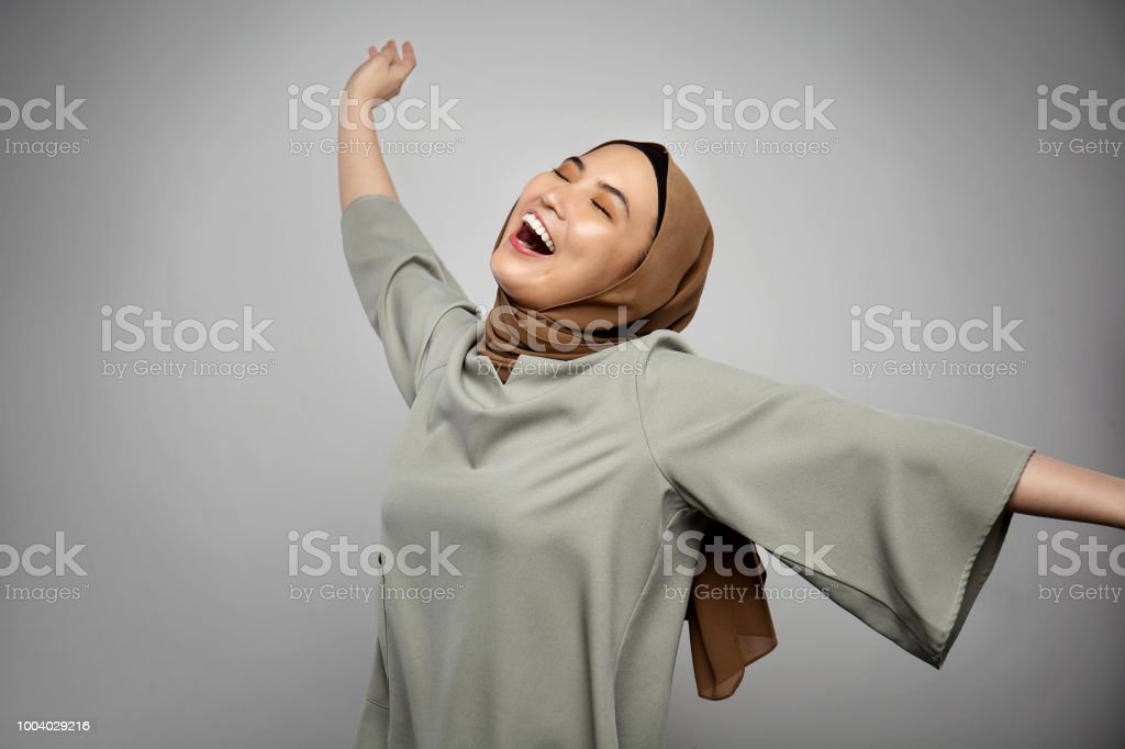 Muslim woman with arms raised outstretched smiling joyful and ecstatic full of happiness with eyes closed isolated on white background stock photo