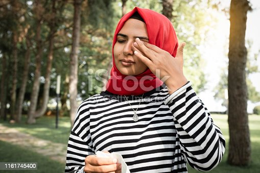 A Woman Alone in the Woodland. Allergy, Sneezing, Muslim Women, Turkey, Eye Fever. Stock Photo of Woman With Pole Allergies, Alone in the woods.  Woman scratching her eyes.
