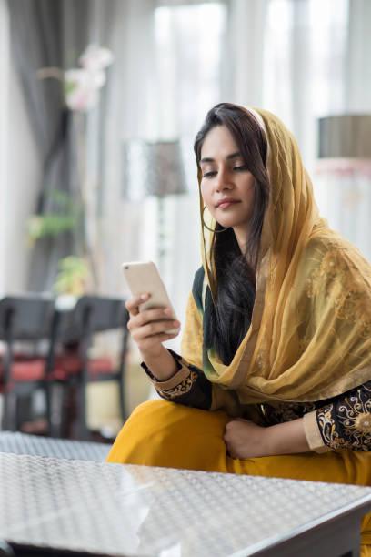 Mujer musulmana con el teléfono móvil en la habitación. - foto de stock