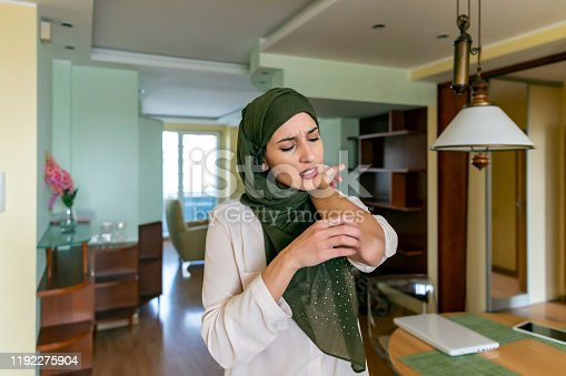 A young Arabian woman is suffering from problems with dermatitis. A Muslim woman is scratching her skin due to insufferable itching problems on her arms at home.