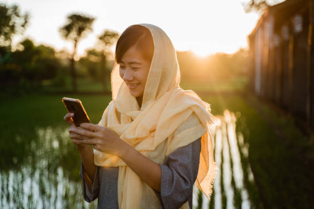 muslim woman with smartphone outdoor stock photo