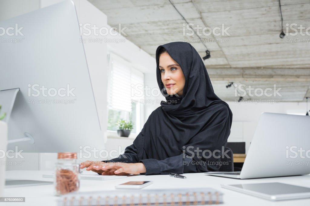 Muslim woman working at her office desk Muslim woman in head scarf sitting at her office desk and working on desktop computer. Adult Stock Photo