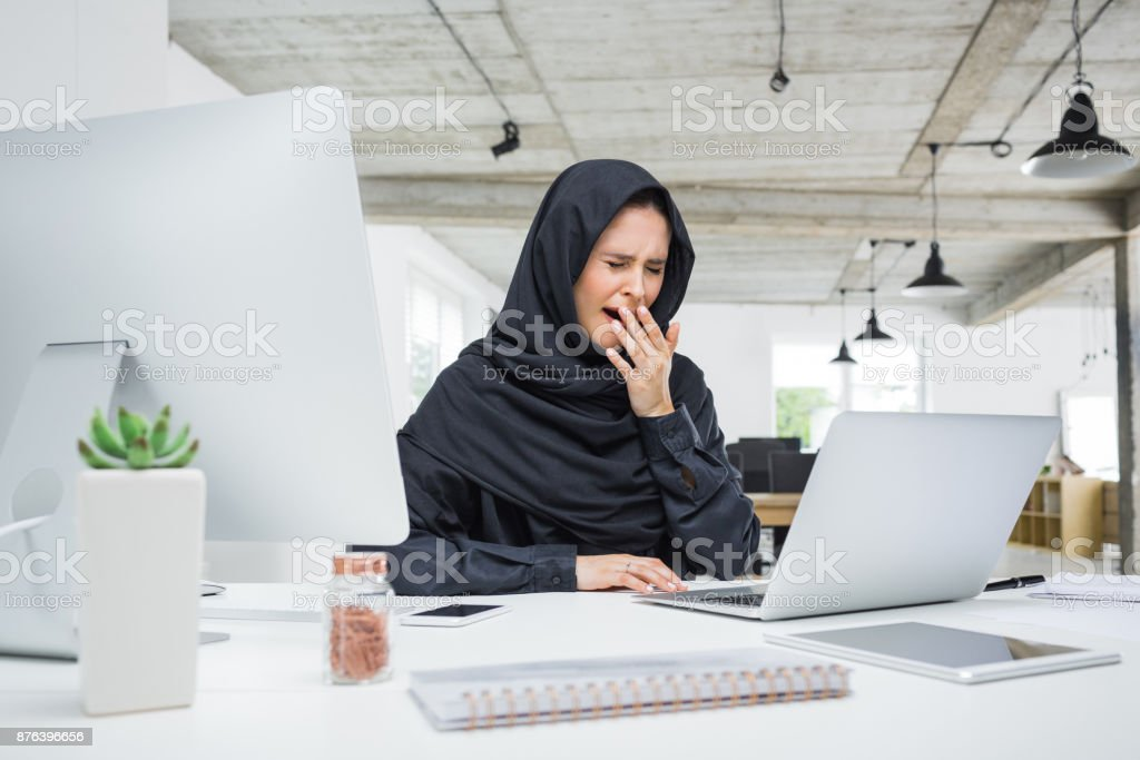 Muslim woman working late in office Muslim business woman working late in her office. Arab female sitting at her work desk and yawning. Adult Stock Photo