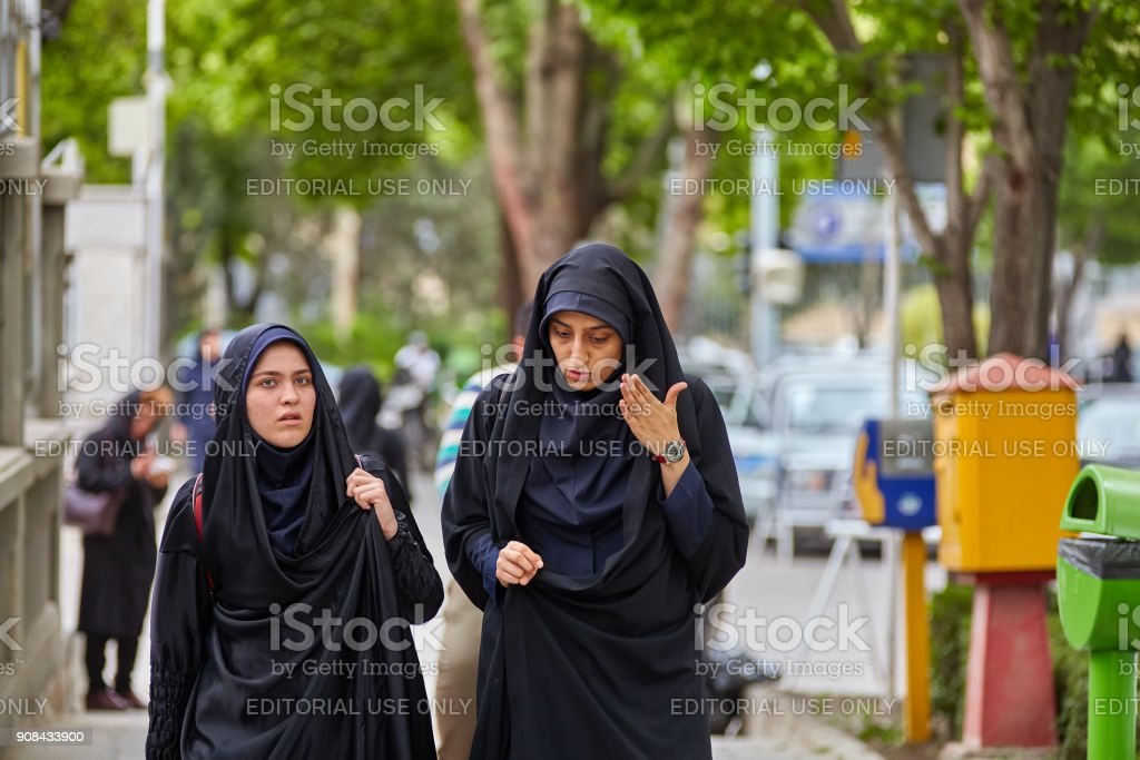 Muslim women in Islamic veil talking on street, Isfahan, Iran. stock photo