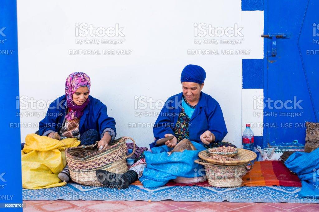 Muslim women making argan oil in traditional way in Morocco. stock photo
