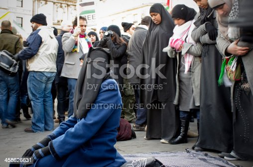 London, UK - January 3, 2009: Muslim Woman Praying in Trafalgar Square, London. The focus is on the keeling woman. She is wearing the Niqab as her head and face are covered with the veil. Behind her, a small group of other Muslims women are standing up in a row and praying as well. They are part of peaceful protesters who are opposed to the Israeli military action in the Gaza Strip.