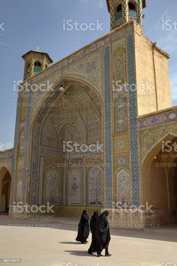 Muslim women wearing black chador in courtyard of Vakil Mosque. stock photo