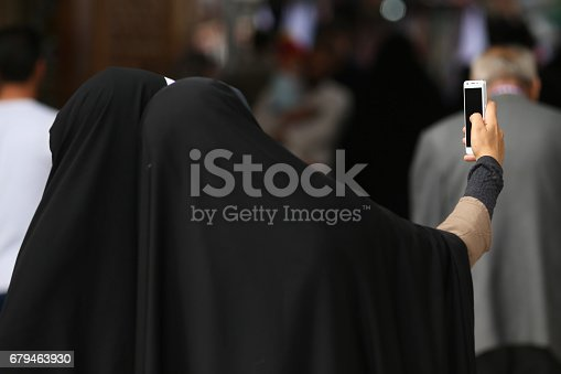 Muslim women with black hijabs posing for a selfie in a mosque in Qom, Iran