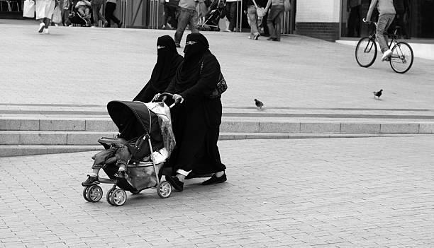 muslimische frauen mit kind im kinderwagen - burka stock-fotos und bilder