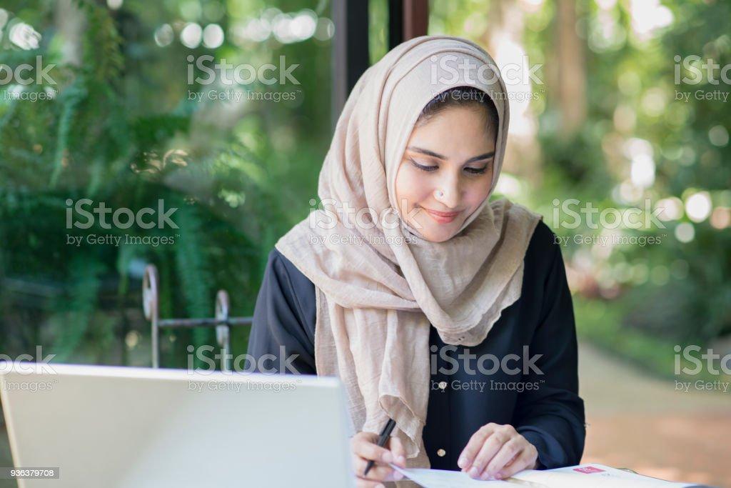 Mujeres musulmanas trabajando en un café y usando computadoras. - foto de stock