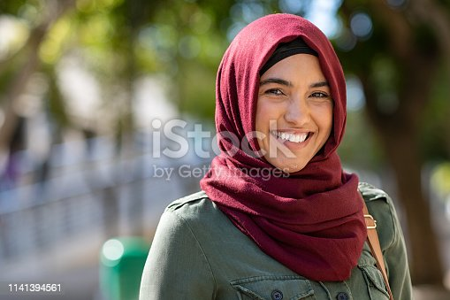 Portrait of young muslim woman wearing hijab head scarf in city while looking at camera. Closeup face of cheerful woman covered with headscarf smiling outdoor. Casual islamic girl at park.