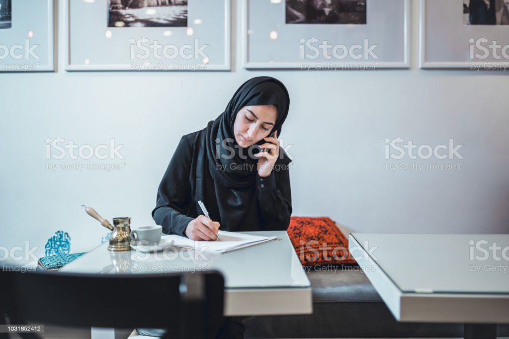 Muslim young woman working at cafe, using mobile phone stock photo