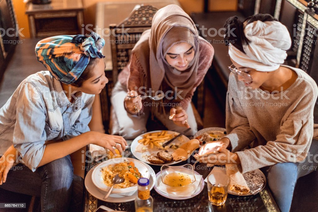 Muslim young women having a lunch break together in an Arab restaurant stock photo