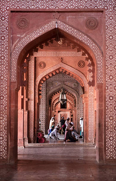 Muslims praying inside Jama Masjid Friday Mosque Agra, India – October 12, 2016: Muslims praying inside the red sandstone doorway and hall of the fort Jama Masjid Friday Mosque in Fatehpur Sikri, Agra, India. Jama Masjid is one of the largest mosques in India. agra jama masjid mosque stock pictures, royalty-free photos & images