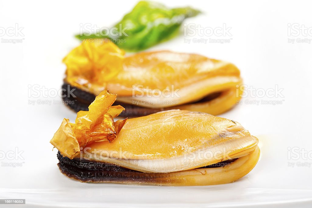 Mussel on the plate, decorated with crispy tomato and basil stock photo