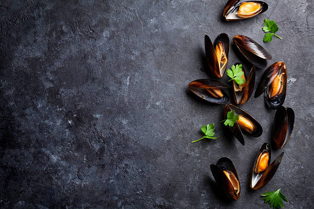 Mussels and parsley Mussels on stone table. Top view with copy space mollusk stock pictures, royalty-free photos & images