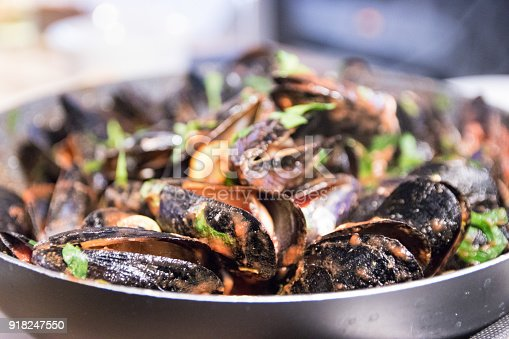 Mussels and shrimps in tomato sauce garnished with parsley