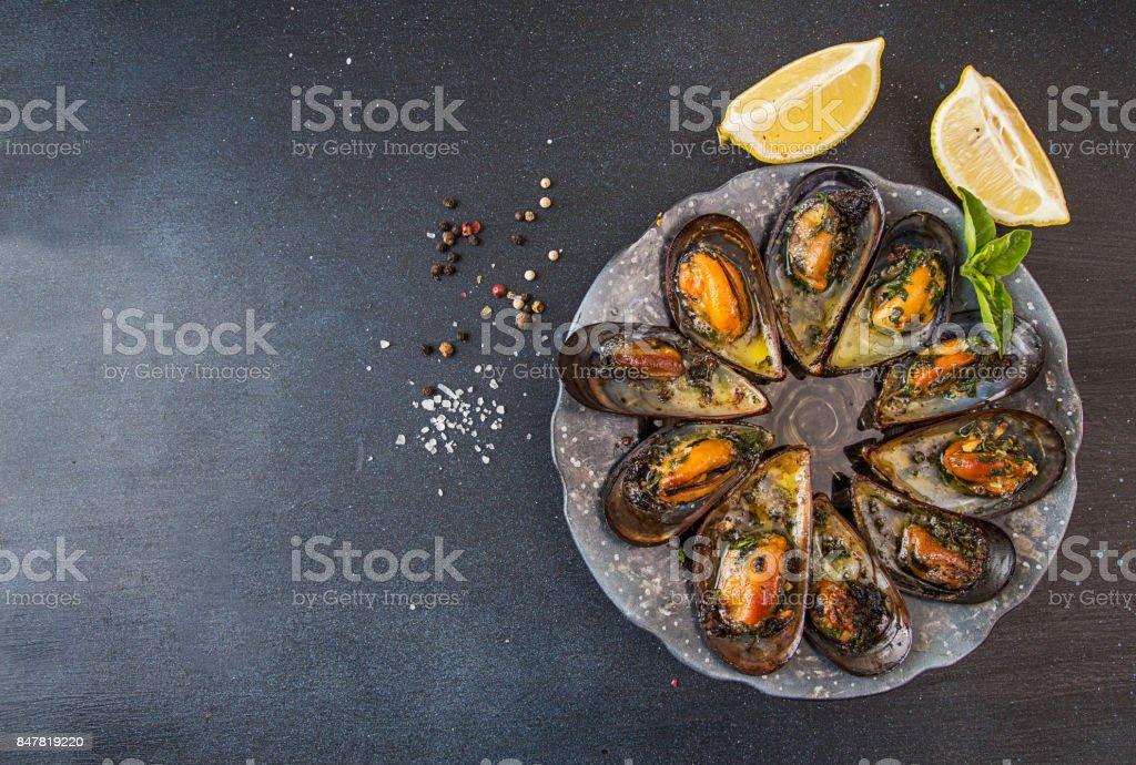 Mejillones al horno con mantequilla y perejil en mejillones de la concha. Limón, perejil y especias alrededor de placa en fondo oscuro. Vista superior. - foto de stock