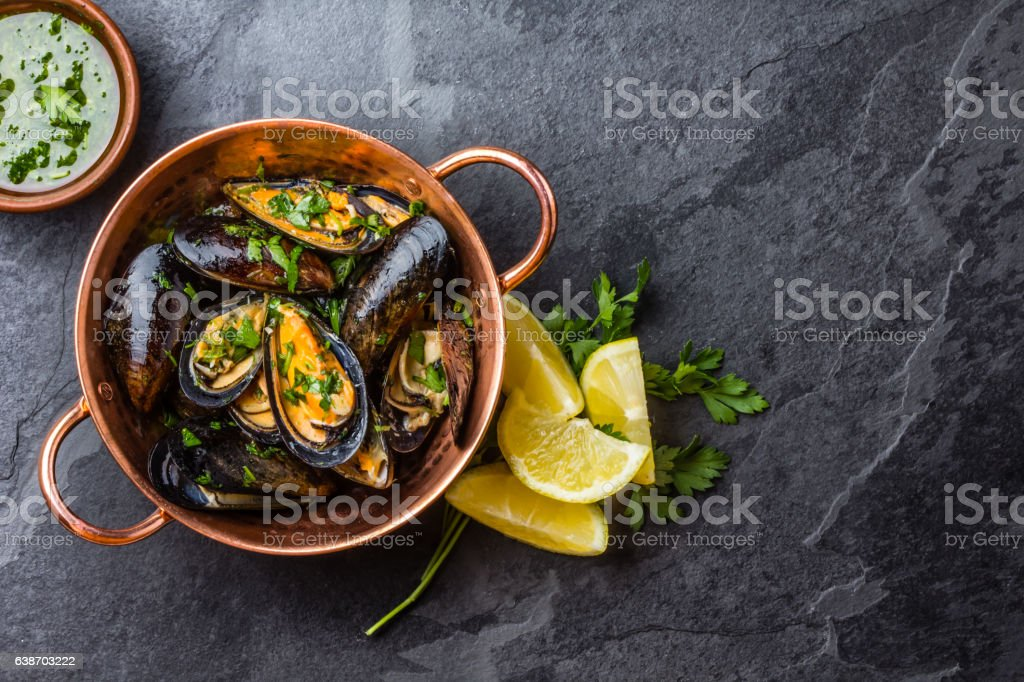 Mussels in copper bowl, lemon, herbs sauce and white wine. ストックフォト