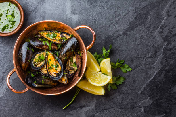 mussels in copper bowl, lemon, herbs sauce and white wine. - steinkraut stock-fotos und bilder