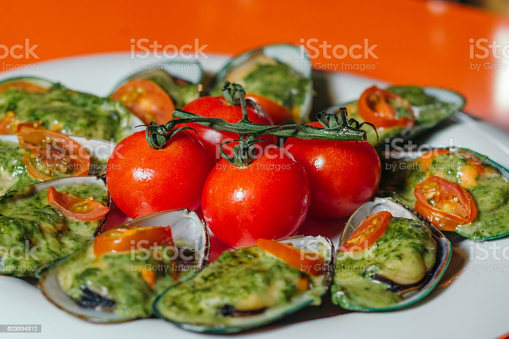 Mussels on a plate with cherry tomatoes. stock photo