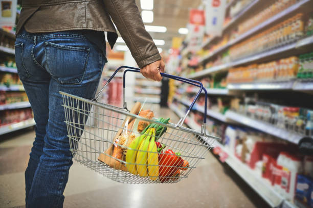 Must stock up Cropped shot of a woman holding a basket while shopping at a grocery store shopping basket stock pictures, royalty-free photos & images