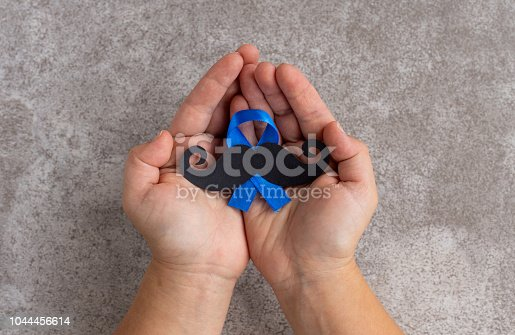 868356038istockphoto Mustache pattern with blue ribbon symbol in child's hands. November movember concept. 1044456614