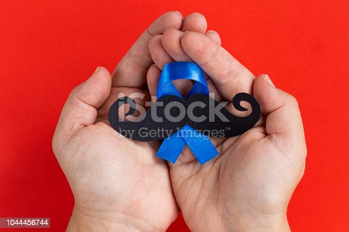 868356038istockphoto Mustache pattern with blue ribbon symbol in child's hands. November movember concept. 1044456744