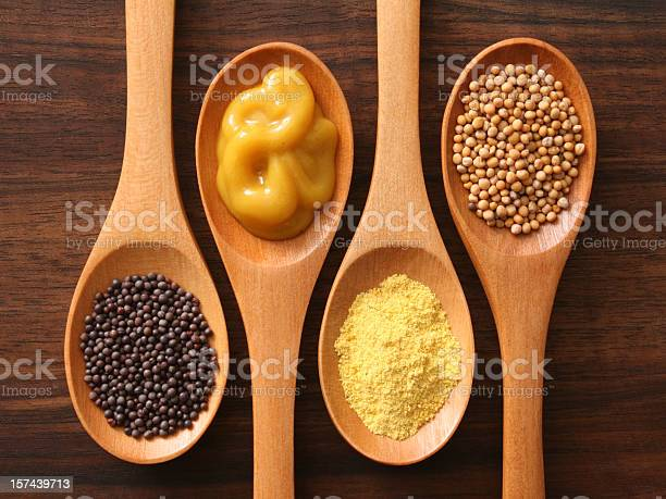 Four spoons with varieties of mustard