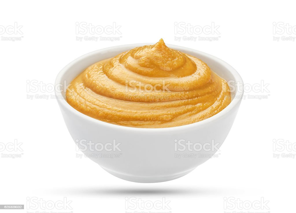 Mustard in bowl isolated on white background stock photo