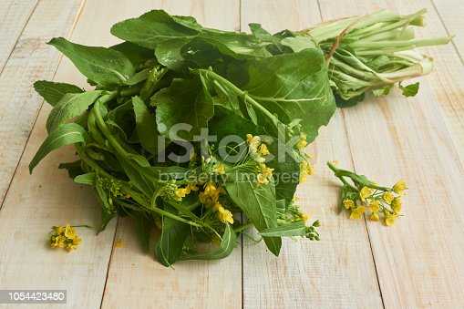 Edible mustard leaves and flowers (brassica juncea) on a wooden rustic table. The leaves and flowers of mustard are known as a very nutritious antioxidant food. Studio shot. High angle view. Close-up. Natural day lighting. Inddors photography. Horizontal composition. Copy space.