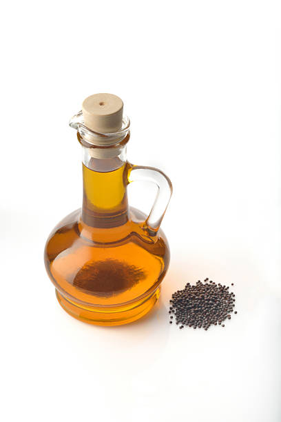 Mustard oil and Seeds on White Background stock photo