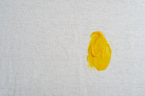 Close up view of mustard stain on cotton fabric of a white T-shirt. Macrophotography image made in studio .