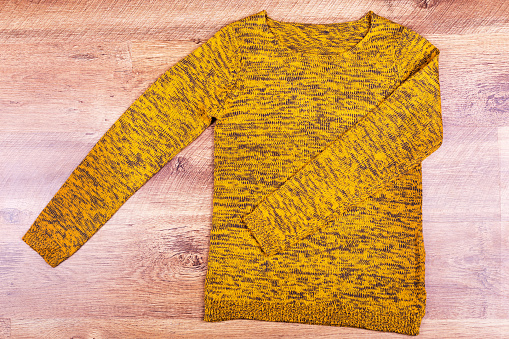 istock Mustard-colored sweater on the floor 1035689104