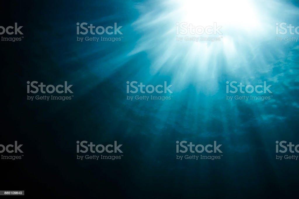 Muted Sun Beams Penetrate Deep Blue Ocean stock photo