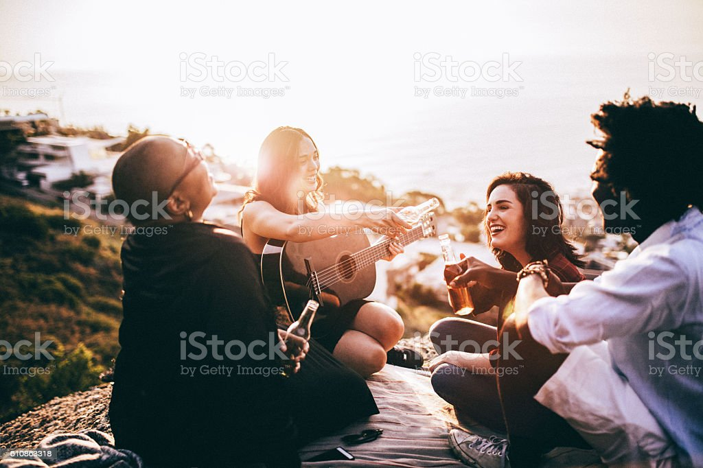 Mutli ethnical group of friends enjoying drinks and playing guit stock photo