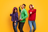 Group of multiracial students with closed eyes listening to music in headphones and dancing together against bright yellow background