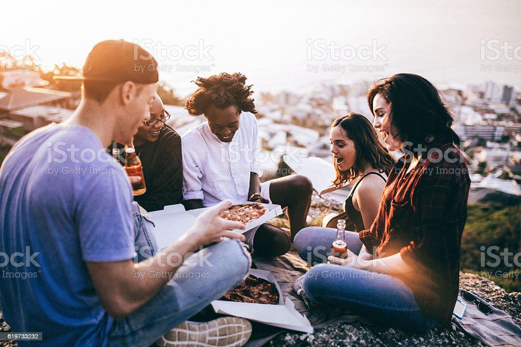 Mutli-ethnical Group enjoying pizza and drinks at sunset - Photo