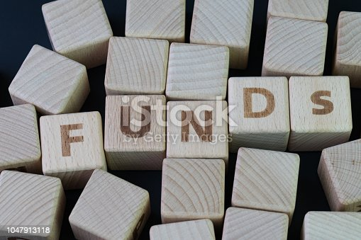 istock Mutual funds, investment asset selection by performance concept, cube wooden block with alphabet combine the word abbreviation FUNDs on black chalkboard background 1047913118
