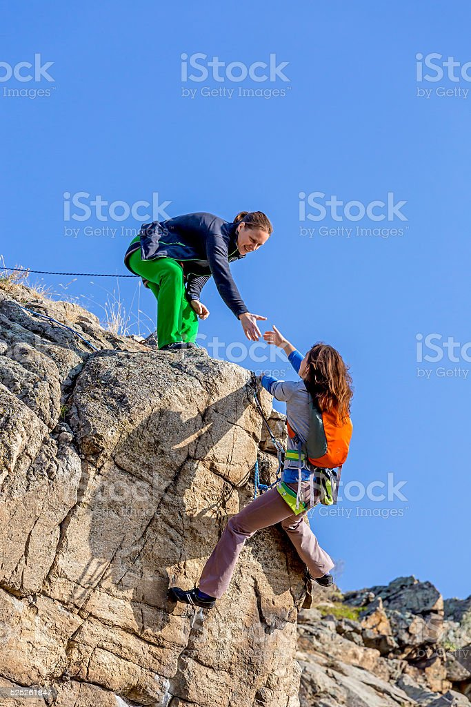 Mutual help between group of climbers stock photo