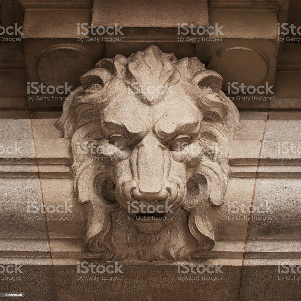 Muzzle ferocious lion carved in stone stock photo